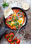 Shakshuka (Fried eggs with tomatoes, bell pepper, vegetables and herbs, Middle eastern traditional dish)
