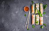Fresh assorted spring rolls set background (with shrimps, vegetables, fruits)