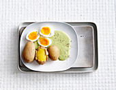 Soft-boiled eggs with green sauce and potatoes