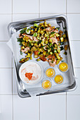 Egg yolks, meat and potatoes on baking tray