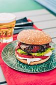 Hausgemachter Cheeseburger mit Tomate und Salat dazu ein Glas Bier