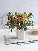 Herbstlicher Strauß mit Hortensienblüten, Hexengras und Büscheln von unreifen Oliven