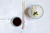 Cooked jasmine rice in a bowl with chopsticks and soy sauce