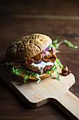 Burger mit Pilzen und Mayonnaiseauf Küchenbrett