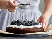 Dusting blackberry cake with powdered sugar