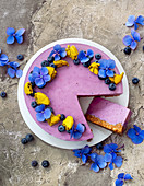 Blueberry and cream cheese cake decorated with macarons and flowers