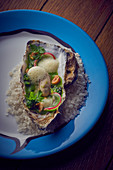 Oyster with foam sauce on a salt bed