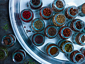 Various spices in glass jars on a tray