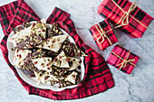 Dark and white chocolate bark with cranberries and pistachios on a dish with small wrapped presents