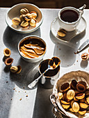 Walnut cookies in a basket with dulce de leche in a bowl and tea cup on gray background