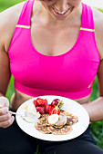Woman holding pancakes with fresh fruits