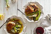Roasted skin-on chicken thighs with leek and wine sauce on white distressed wooden table