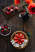 Strawberry tart with poppy flowers on a wooden table