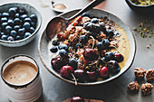 Healthy vegan breakfast set: Quinoa oat granola coconut yogurt bowl with fruit, seeds, nuts, berries and coffee