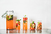 Homemade strawberry and basil lemonade or ice tea in glass tumblers with eco-friendly plastic-free straws on grey concrete table