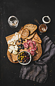 Grilled pieces of bread, cheese variety, salami slices, olives, apricot jam, berries and white wine over rustic black background