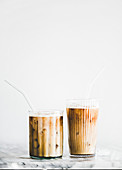 Homemade iced latte coffee in glasses with straws on marble table, white wall at background