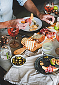 Charcuterie and cheese board, rose wine, nuts, olives, fresh fruits and mans hands with food