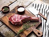 Rohes Tomahawk-Steak vom Angusrind auf Holzbrett