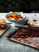 BBQ smoked glazed grilled pork ribs on rustic background with roasted potatoes and cereal bread
