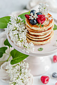 Pancakes stack with raspberries, blueberries, mint and lilac