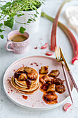 Pancakes with caramelized rhubarb, sprinkled with strawberry powder