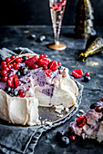 Pavlova cake with forest fruit and mascarpone, champagne in the background