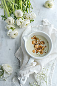 Pudding with macadamia nuts and cashews served in a white pot
