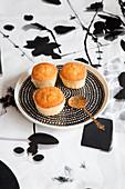 Muffins auf Teller und schwarz-weißem Tischtuch