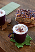 Cocoa with cream in brown cups on autumn felt coasters
