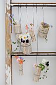 Mit Buchseiten umhüllte Gläser mit Blumen hängen im alten Fenster
