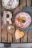 Country-house plates, decorative letter, heart-shaped pendant and candle on rustic wooden table