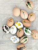 Mit gepressten Blättern, Blüten und Federn beklebte Ostereier