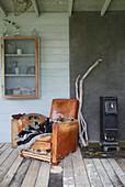 Alter Ledersessel neben Holzofen und Wandschrank im Gewächshaus