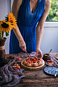 Woman cutting rustic apricot galette