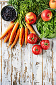 Stilleben mit frischem Obst und Gemüse auf weißem Holzuntergrund