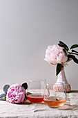 Two glasses of different rose wine standing on grey linen table cloth with pink peonies flowers