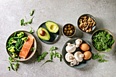 Ketogenic diet ingredients for cooking dinner. Raw salmon, avocado, broccoli, bean, olives, nuts mushrooms, eggs in ceramic bowls