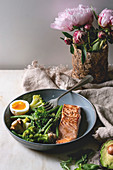 Ketogenic low carb diet dinner grilled salmon, avocado, broccoli, green bean and soft boiled egg in ceramic bowl