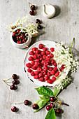 Fresh cherry and raspberry berries in ceramic mug and plate, elderflowers, jug of cream