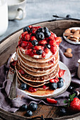 A close up shot of gluten free pancakes with berries