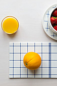 Orange on blue-and-white checked board and glass of orange juice
