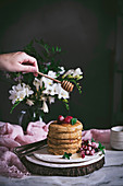 Stack of raspberry pancakes with fresh berry and dripping honey on porcelain plate at marble tabletop
