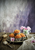 Plate with tasty grain muffins placed near linen napkin and pink flowers on wooden tabletop
