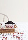 Porcelain cup full of dried tea leaves placed on wooden tray near flower petals on table in morning