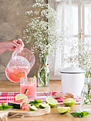 Iced pink drink with watermelon and lime slices pouring into glass from cold jar on rustic kitchen table and bunch of gypsophila flowers