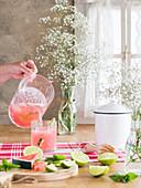 Rosa Limonade mit Wassermelonen- und Limettenscheiben in Glas einschenken
