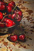 From above tasty appetizing ripe cherry in black brown shining under sunlight on rustic background