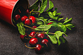 Ripe tasty red cherry with green stem and branches in red cup with shiny side on table
