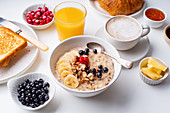 Breakfast with oatmeal with berries and nuts, croissants, toasts with jam and butter, coffee and orange juice